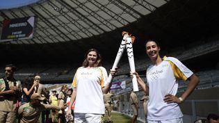 Lesvolleyeuses brésiliennes Ana Flavia (aujourd'hui retraitée) et Sheilla Castro avec la flamme olympique, le 14 mai 2016 au stade Mineirao de Belo Horizonte (Brésil). (DOUGLAS MAGNO / AFP)