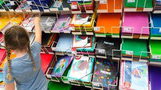 Une enfant choisit des fournitures scolaires dans un supermarché de Valence (Drôme), le 23 août 2019,avant la rentrée des classes. (NICOLAS GUYONNET / HANS LUCAS / AFP)