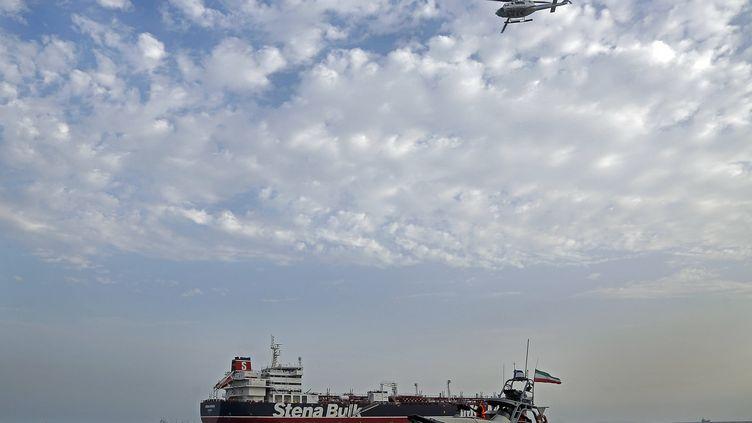 """Une navette et un hélicoptère des Gardes de la Révolution iraniens autour du """"Stena Impero"""", un tanker à pavillon britannique saisi par l'Iran, ici le 21 juillet 2019 dans le golfe Persique. (HASAN SHIRVANI / AP / SIPA)"""