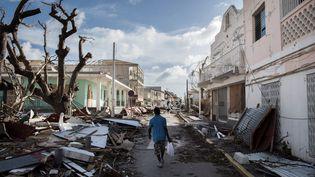 Un homme marche dans les rues de l'île de Saint-Martin dévastée par le passage de l'ouragan Irma, le 8 septembre 2017. (MARTIN BUREAU / AFP)