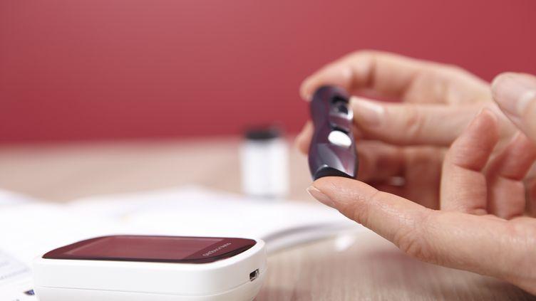 Une femme contrôle le taux de glucose dans son sang, en septembre 2015. (THEOBALD / BSIP / AFP)