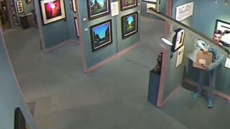 Capture d'écran d'une videosurveillance publiée par la police deBirmingham (Royaume-Uni) montrant un visiteur d'uen galerie d'art dérobé un tableau, le 17 aout 2014. (NEWSFORALL / YOUTUBE)