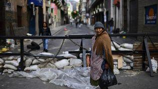 Une Bolivienne traverse une rue bloquée par une barricade, à La Paz (Bolivie), le 12 novembre 2019. (RONALDO SCHEMIDT / AFP)