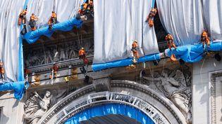 Les cordistes, en rappel, déploient le tissu en polypropylène fabriqué spécialement en Allemagne. Il est bleu côté pile et argenté côté face,. Un kilo d'aluminium a été puvérisé sur les 25 000 m2 d'étoffe qui emballent le monument. (THOMAS SAMSON / AFP)