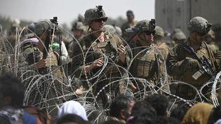 Des soldats américains montent la garde derrière des barbelés à l'aéroport de Kaboul en Afghanistan, le 20 août 2021. (WAKIL KOHSAR / AFP)
