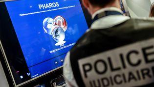 Un policier devant la plateforme de signalement Pharos, le 23 janvier 2018, à Lille (Nord).  (PHILIPPE HUGUEN / AFP)