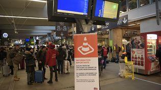 Des passagers devant les panneauxd'affichage de la gare Montparnasse à Paris, le 3 décembre 2017. (MARTIN BUREAU / AFP)