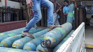 Des bouteilles d'oxygène sont chargées sur un camion à destination des hôpitaux à Bangalore, dans le sud de l'Inde, le 5 mai 2021. (MANJUNATH KIRAN / AFP)