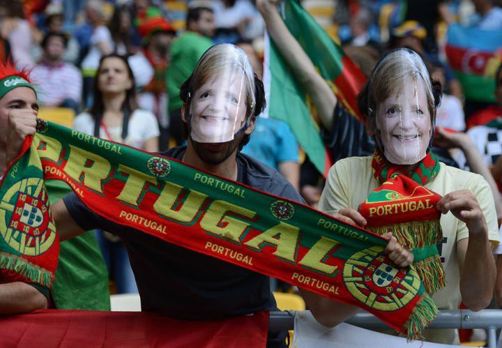 Des supporters portugais portant des masques à l'effigie de la chancelière allemande Angela Merkel, le 13 juin 2012. (JEFF PACHOUD / AFP)