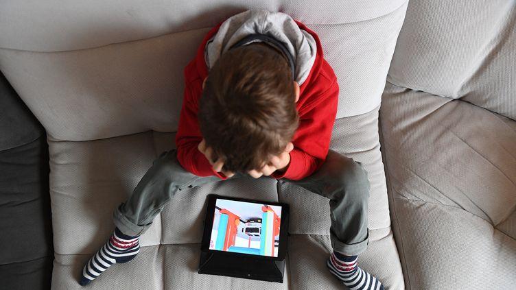 Un enfant regarde un écran assis sur son canapé. Photo d'illustration. (JOSSELIN CLAIR / MAXPPP)