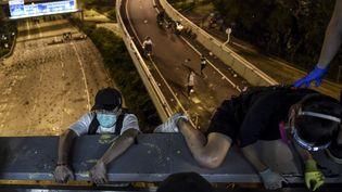 Encerclés par la police, des manifestants quittent l'université polytechnique de Hong Kong en descendant en rappel d'une passerelle, le 18 novembre 2019 au soir. (YE AUNG THU / AFP)