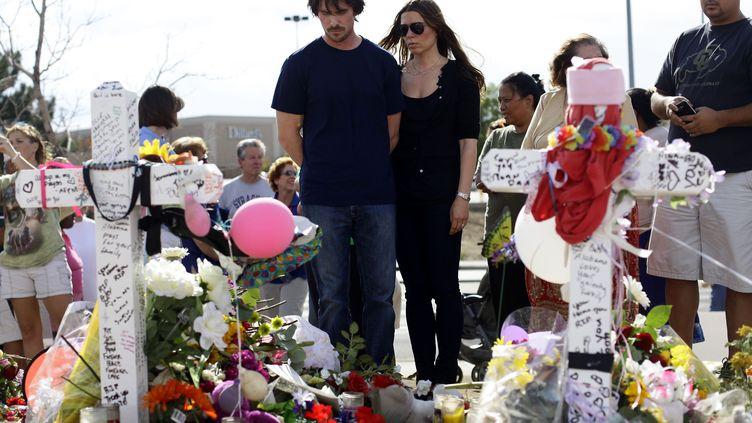 L'acteur Christian Bale et sa femme Sandra Blažićse recueillent devant le mémorial dressé en hommage aux 12 personnes tuées lors d'une fusillade dans un cinéma d'Aurora (Colorado), le 24 juillet 2012. (JOSHUA LOTT / GETTY IMAGES)