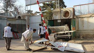 Des employés afghans de MSF déplacent la porte détruite de l'enceinte de leur hôpital à Kunduz (Afghanistan), le 15 octobre 2015. (NAJIM RAHIM / AP / SIPA)