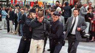Maxime Brunerie interpellé par des policiers au milieu des Champs-Elysées, aprèsqu'il a tenté d'assassiner Jacques Chirac, le14 juillet 2002,à Paris. (AFP)