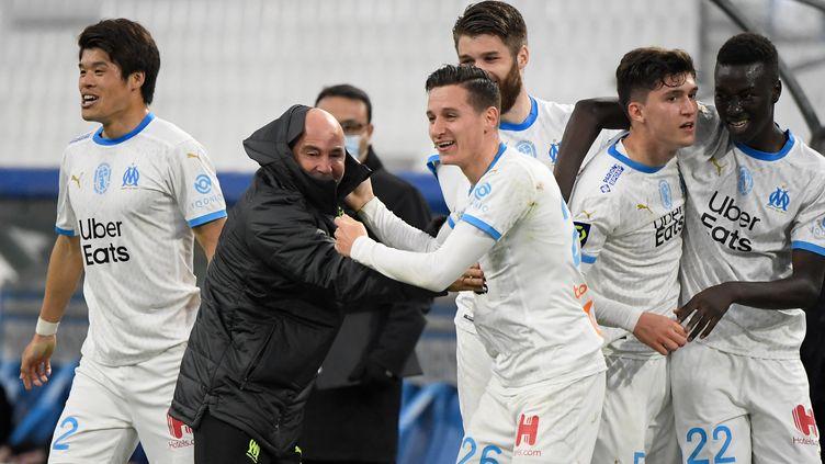 Florian Thauvin fête son but avec Jorge Sampaoli face à Brest, samedi 13 mars 2021. (NICOLAS TUCAT / AFP)