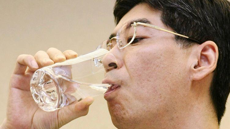 Le député japonaisYasuhiro Sonoda boit un verre d'eau provenant de l'intérieur de la centrale nucléaire accidentée de Fukushima, à Tokyo (Japon), le 31 octobre 2011. (JIJI PRESS / AFP)