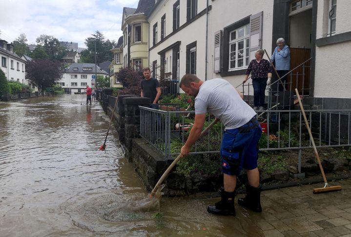 Des habitants de Mayen en Allemagne pompent l'eau de leur rue après des intempéries, le 15 juillet 2021. (MICHELLE FITZPATRICK / AFP)