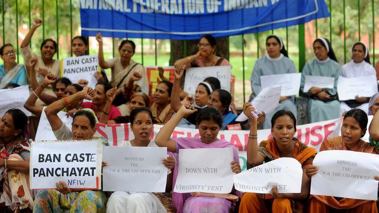 Des militantes indiennes tenant des pancartes au cours d'une manifestation organisée devant le parlement, à New Delhi (Inde), le 29 juillet 2009 pour protester contre les tests de virginité menés dans les Etats du Madhya Pradesh et du Kerala. (RAVEENDRAN / AFP)