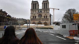 Des touristes observent la cathédrale Notre-Dame de Paris, encore en travaux, le 8 janvier 2020. (MAXPPP)