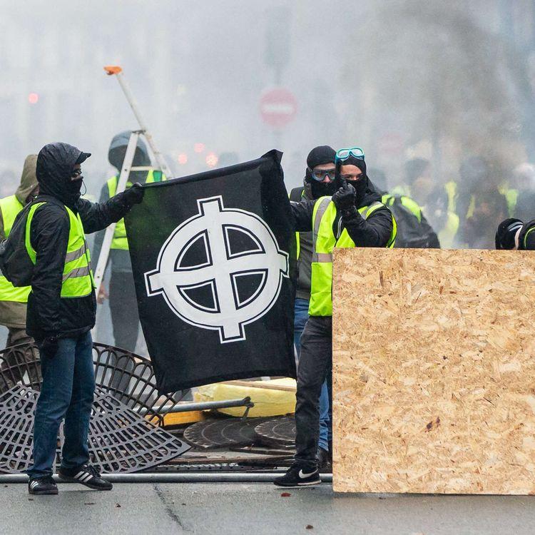 """Des manifestants vêtus d'un """"gilet jaune"""" dressent un drapeau avec une croix celtique, un symbole d'extrême droite, à Paris, le 1er décembre 2018. (LUKE DRAY/COVER IMAGES/SIPA)"""