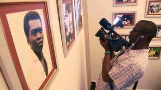 Un vidéaste filme des photographies de la légende de la musique nigériane, Fela Kuti, lors de la cérémonie d'ouverture d'un musée en son honneur à Lagos le 15 octobre 2012. Kuti, militant des droits de l'Homme et pionnier de la musique afrobeat, est mort de complications liées au sida en 1997. (AKINTUNDE AKINLEYE / REUTERS)