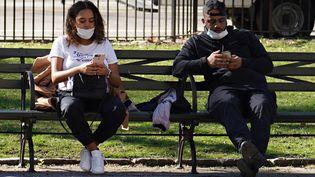 Deux personnes portant un masque de protection sont assises sur un banc, à New York, le 27 mars 2020. (CINDY ORD / GETTY IMAGES NORTH AMERICA / AFP)