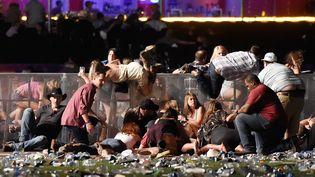 Des spectateurs tentent de se mettre à l'abri lors de la fusillade survenue à Las Vegas (Etats-Unis), qui a fait au moins 50 morts et 400 blessés, le 1er octobre 2017. (DAVID BECKER / GETTY IMAGES NORTH AMERICA / AFP)