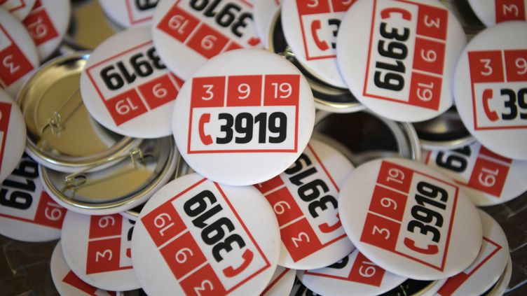 Des badges avec le numéro d'urgence 3919, créé pour lutter contre les violences conjugales. (ERIC FEFERBERG / AFP)