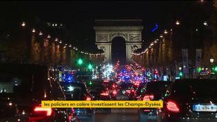 Des policiers manifestent en voiture sur les Champs-Elysées, dans la nuit du 17 au 18 octobre 2016. (FRANCEINFO)
