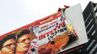 """Une affiche du film """"The Interview"""" en train d'être retirée à Hollywood (Etats-Unis), le 18 décembre 2014. (VERONIQUE DUPONT / AFP)"""