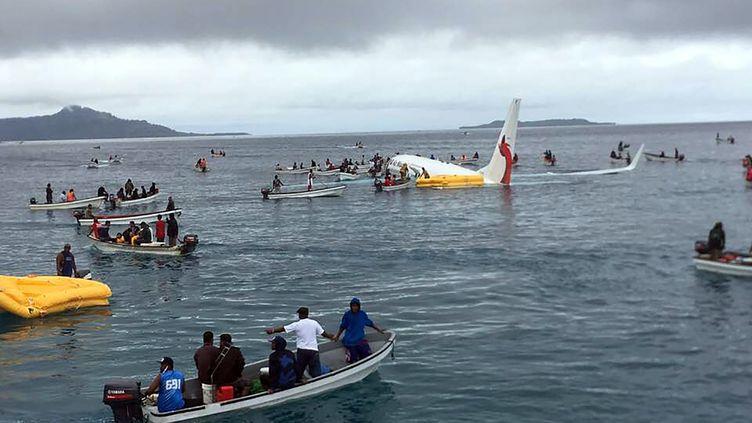 Cette photo de James Yaingeluo montre des habitants qui viennent en aide aux passagers de l'avion d'Air Niugini qui a amerri le 28 septembre 2018 près de l'île de Weno (Micronésie). (JAMES YAINGELUO / AFP)
