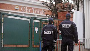 Deux policiers montent la garde devant l'école juive Ohr Torah, le 6 février 2013, à Toulouse (Haute-Garonne). (REMY GABALDA / AFP)