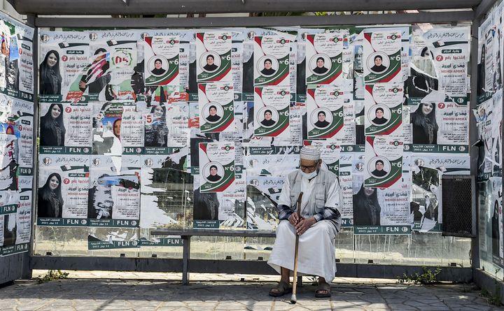 """11 juin 2021, la veille des élections législatives en Algérie. Un vieil homme assis dans une station de bus, avec les affiches électorales du candidat du """"Front du futur"""". (RYAD KRAMDI / AFP)"""
