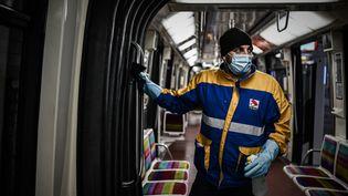 Un nettoyeurporte un masque et des gants pour désinfecter le métro à Vincennes, près de Paris. (PHILIPPE LOPEZ / AFP)