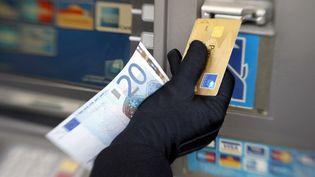Une personne retire de l'argent avec une carte bleue à un distributeur automatique deNice (Alpes-Maritimes), le 5 février 2013. (VALERY HACHE / AFP)