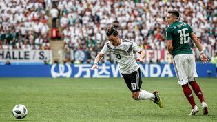 Le meneur de jeu allemand Mesut Özil chute devant un panneau publicitaire en mandarin, lors du match Allemagne-Mexique, le 17 juin 2018 à Moscou (Russie). (PACIFIC PRESS / LIGHTROCKET)