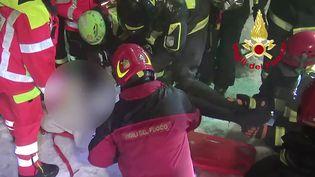 Des pompiers en train d'extraire une personne enfouie sous les décombres le 21 janvier 2017 près de Farindola (Italie). (AFP)