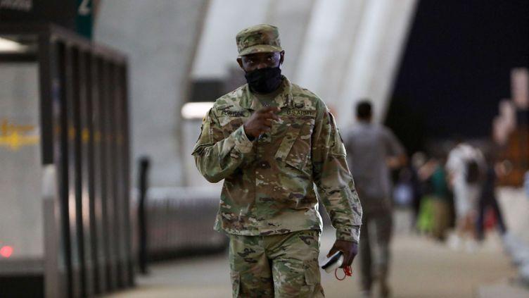 Les forces de sécurité montent la garde alors que des réfugiés afghans arrivent à l'aéroport international de Washington (Etats-Unis), le 27 août 2021. (Yasin Ozturk / ANADOLU AGENCY / AFP)