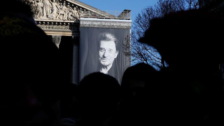 Un immense portrait de Johnny Hallyday a été installée sur la façade de l'église de la Madeleine. Une scène a été aménagée au pied de l'église, pour permettre à des musiciens de rendre hommage au chanteur en musique. (PASCAL ROSSIGNOL / REUTERS)