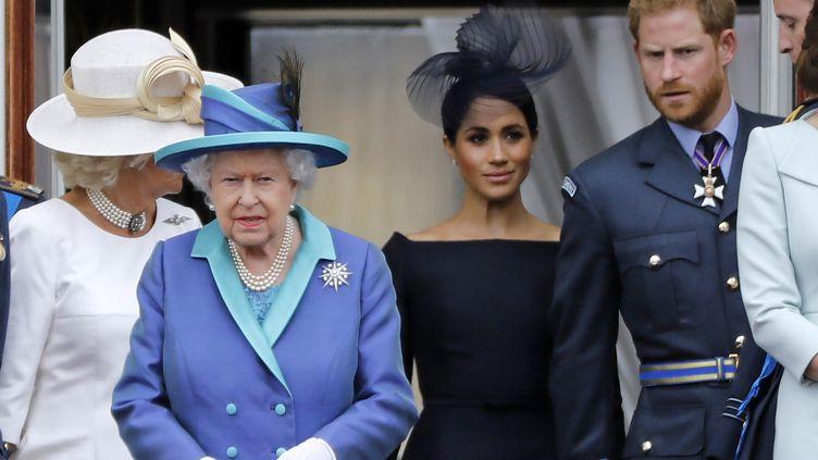 La reine Elizabeth II, Meghan Markle et le prince Harry le 10 juillet 2018, à Londres, lors d'une cérémonie pour le centenaire de la Royal Air Force. (TOLGA AKMEN / AFP)
