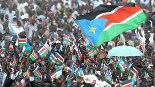 Surcette photo prise le 9 juillet 2011, des milliers de Sud-Soudanais brandissent le drapeau de leur pays lors d'une cérémonie dans la capitale Juba pour célébrer la proclamation de l'indépendance du Soudan du Sud. (ROBERTO SCHMIDT / AFP)