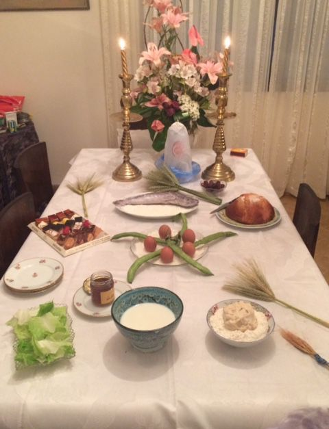Table de mimouna sur laquelle on retrouve du miel, le leben (petit-lait fermenté), une boule de levain, l'assiette de farine sur laquelle sont posées les 5 fèves et les 5 œufs, un poisson, un pain de sucre, des gâteaux, des épis de blé. (photo d'Har)