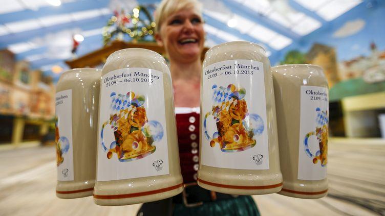 Une serveuse présente les chopes de bière officielles de l'Oktoberfest, la fête de la bière à Munich (Allemagne), le 27 août 2013. (MICHAEL DALDER / REUTERS)