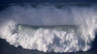 Un surfer sur les vagues de Nazaré qui ont frappé les côtes de la Praia do Norte (Portugal) le 11 décembre 2014. (FRANCISCO LEONG / AFP)