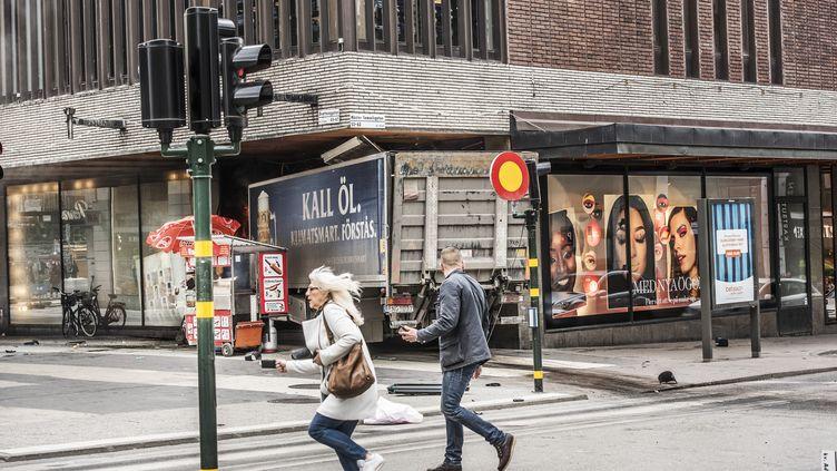 Des passants s'enfuient alors qu'un camion s'est encastré dans le mur d'un centre commercial surDrottninggatan, au centre de Stockholm, le 7 avril 2017. (TOMAS ONEBORG/SVD / TT NEWS AGENCY / AFP)