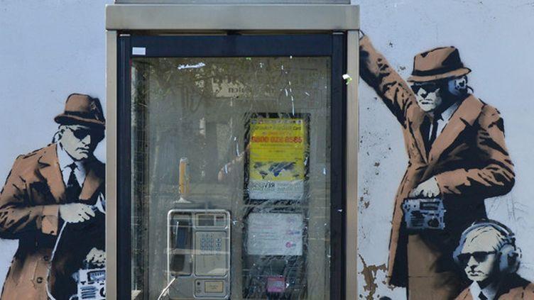 L'oeuvre de Banksy apparue à Cheltenham le 13 avril 2014, montrant des agents gouvernementaux espionnant une cabine téléphonique.  (Jules Annan/Photoshop/MAXPPP )