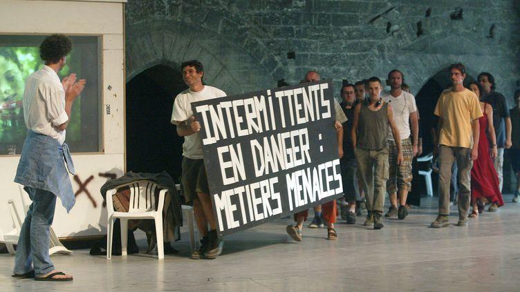 Le metteur en scène Alain Platel applaudit les manifestants sur scène, lors d'une précdente grève au festival d'Avignon, le 7 juillet 2003. (GERARD JULIEN / AFP)