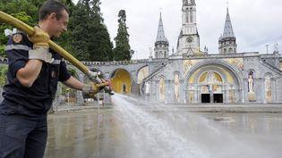 Un pompier en opération de nettoyage à Lourdes. Les sanctuaires ont été lourdement endommagés par le débordement du Gave de Pau. (PASCAL PAVANI / AFP)