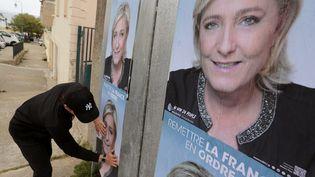 Un miltant colle des affichesde Marine Le Pen à Ajaccio, en Corse. (PASCAL POCHARD-CASABIANCA / AFP)