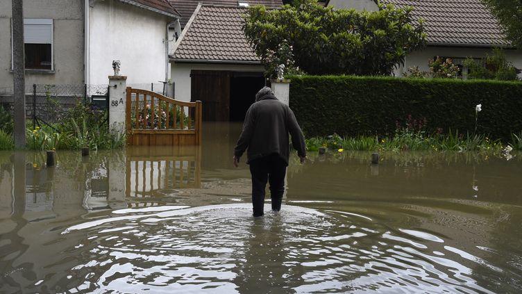 Un habitant de Nemours (Seine-et-Marne) marche dans une rue inondée, le 1er juin 2016. (DOMINIQUE FAGET / AFP)